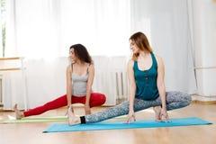Δύο όμορφα λεπτά κορίτσια που κάνουν τις τεντώνοντας ασκήσεις στη γυμναστική Στοκ Φωτογραφίες