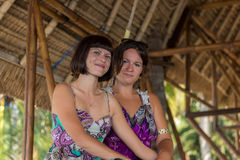 Δύο όμορφα ευτυχή νέα κορίτσια που κάθονται σε ένα ξύλινο gazebo στην ηλιόλουστη ημέρα και κατοχή της διασκέδασης, χαμόγελο και γ στοκ φωτογραφίες