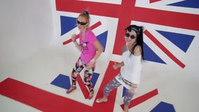 Δύο όμορφα θηλυκά στις μπλούζες κοιτάζουν επίμονα στη κάμερα και συγχρονικά το χορό απόθεμα βίντεο