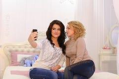 Δύο όμορφα κορίτσια κάνουν selfie τη φωτογραφία, χρησιμοποιώντας τη συσκευή, για τη μνήμη, Στοκ Εικόνες