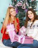 Δύο όμορφα κορίτσια καλύτερων φίλων που ανοίγουν τα χριστουγεννιάτικα δώρα κοντά στο θόριο Στοκ Φωτογραφίες