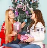 Δύο όμορφα κορίτσια καλύτερων φίλων που ανοίγουν τα χριστουγεννιάτικα δώρα κοντά στο θόριο Στοκ φωτογραφίες με δικαίωμα ελεύθερης χρήσης