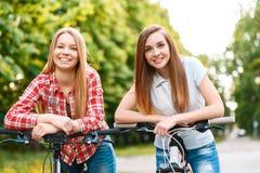 Δύο όμορφα κορίτσια κοντά στα ποδήλατα Στοκ εικόνες με δικαίωμα ελεύθερης χρήσης
