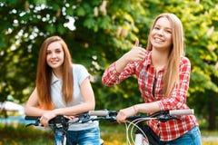 Δύο όμορφα κορίτσια κοντά στα ποδήλατα Στοκ Εικόνα