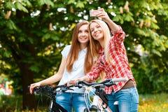 Δύο όμορφα κορίτσια κοντά στα ποδήλατα Στοκ φωτογραφία με δικαίωμα ελεύθερης χρήσης