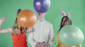 Δύο όμορφα κορίτσια με τα αστεία καπέλα και νεαρός άνδρας που χορεύει στο πράσινο υπόβαθρο απόθεμα βίντεο