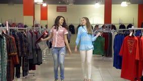 Δύο όμορφα κορίτσια με τις τσάντες αγκαλιάζουν και περπατούν στο κατάστημα φιλμ μικρού μήκους