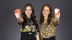 Δύο όμορφα κορίτσια παρουσιάζουν κόκκινη καρδιά απόθεμα βίντεο