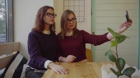 Δύο όμορφα κορίτσια που θέτουν για ένα selfie τον εσωτερικό καφέ απόθεμα βίντεο