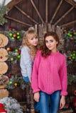 Δύο όμορφα κορίτσια που θέτουν στις διακοσμήσεις Χριστουγέννων Στοκ Φωτογραφίες