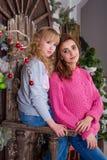 Δύο όμορφα κορίτσια που θέτουν στις διακοσμήσεις Χριστουγέννων Στοκ Εικόνες