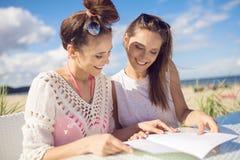 Δύο όμορφα κορίτσια που κάθονται στον πίνακα καφέδων στις επιλογές ανάγνωσης παραλιών Στοκ Εικόνες