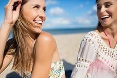 Δύο όμορφα κορίτσια που κάθονται στο γέλιο παραλιών Στοκ Εικόνες