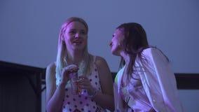 Δύο όμορφα κορίτσια που πίνουν τα κοκτέιλ σε ένα νυχτερινό κέντρο διασκέδασης Δύο χαριτωμένες φίλες κάθονται με τα κοκτέιλ και κο απόθεμα βίντεο
