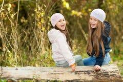 Δύο όμορφα κορίτσια που φορούν μια beret συνεδρίαση στην τοποθέτηση κούτσουρων Στοκ εικόνες με δικαίωμα ελεύθερης χρήσης