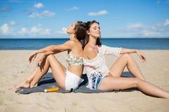 Δύο όμορφα κορίτσια που χαλαρώνουν στην ηλιοθεραπεία παραλιών Στοκ Εικόνες