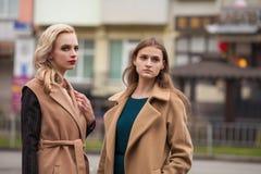 Δύο όμορφα κορίτσια σε ένα παλτό φθινοπώρου Στοκ Φωτογραφίες