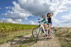 Δύο όμορφα κορίτσια στο γύρο ποδηλάτων στην πορεία στοκ εικόνες