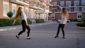 Δύο όμορφα κορίτσια χορευτών μπαλέτου ασκούν την απόδοσή τους μπροστά από τα σύγχρονα σπίτια διαβίωσης σε μια πόλη το βράδυ φιλμ μικρού μήκους