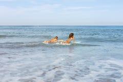 Δύο όμορφα κορίτσια surfer στην παραλία πηγαίνουν στο νερό Στοκ Εικόνες