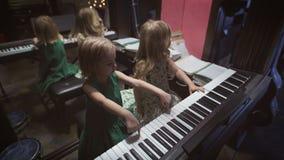 Δύο όμορφα μικρά κορίτσια παίζουν το πιάνο σε ένα δωμάτιο απόθεμα βίντεο