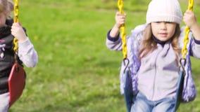 Δύο όμορφα μικρά κορίτσια σε μια ταλάντευση υπαίθρια στην παιδική χαρά απόθεμα βίντεο