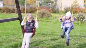 Δύο όμορφα μικρά κορίτσια σε μια ταλάντευση υπαίθρια στην παιδική χαρά φιλμ μικρού μήκους