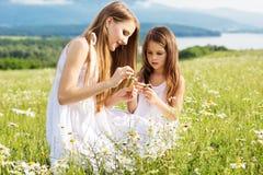 Δύο όμορφα μικρά κορίτσια στο λιβάδι των chamomiles Στοκ Φωτογραφίες