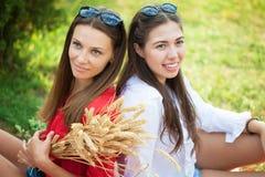 Δύο όμορφα νέα κορίτσια κάθονται σε ένα θερινό πικ-νίκ σε ένα πάρκο στοκ εικόνα