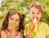 Δύο όμορφα νέα κορίτσια, που τρώνε ένα υγιείς μήλο και μια μπανάνα σε ένα υπόβαθρο κήπων Στοκ Εικόνα