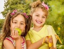Δύο όμορφα νέα κορίτσια, που τρώνε ένα υγιείς μήλο και μια μπανάνα σε ένα υπόβαθρο κήπων Στοκ εικόνα με δικαίωμα ελεύθερης χρήσης