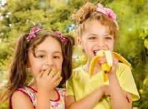 Δύο όμορφα νέα κορίτσια, που τρώνε ένα υγιείς μήλο και μια μπανάνα σε ένα υπόβαθρο κήπων Στοκ Εικόνες