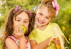 Δύο όμορφα νέα κορίτσια, που τρώνε ένα υγιείς μήλο και μια μπανάνα σε ένα υπόβαθρο κήπων Στοκ εικόνες με δικαίωμα ελεύθερης χρήσης