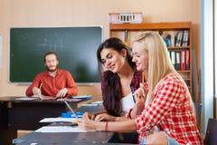 Δύο όμορφα νέα κορίτσια που χρησιμοποιούν το γυμνάσιο υπολογιστών ταμπλετών, χαμογελώντας το ελεγχμένο ένδυση πουκάμισο σπουδαστώ Στοκ Φωτογραφία
