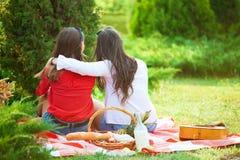 Δύο όμορφα νέα κορίτσια σε ένα πικ-νίκ το καλοκαίρι στο πάρκο που διοργανώνει τη διασκέδαση και την ομιλία στοκ φωτογραφία με δικαίωμα ελεύθερης χρήσης