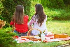 Δύο όμορφα νέα κορίτσια σε ένα πικ-νίκ το καλοκαίρι στο πάρκο που διοργανώνει τη διασκέδαση και την ομιλία στοκ εικόνες με δικαίωμα ελεύθερης χρήσης