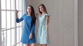 Δύο όμορφα πρότυπα στα μπλε και ανοικτό μπλε φορέματα που θέτουν στη φωτογραφία καταλόγων απόθεμα βίντεο