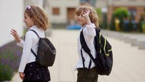 Δύο όμορφα σγουρός-μαλλιαρά παιδιά, ένα αγόρι και ένα κορίτσι, πηγαίνουν στο σχολείο Γυρίζουν και κυματίζουν τα χέρια τους στο χω φιλμ μικρού μήκους