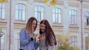 Δύο όμορφα χαμογελώντας κορίτσια εξετάζουν το τηλέφωνο στο πάρκο φθινοπώρου κοντά στο πανεπιστήμιο φιλμ μικρού μήκους