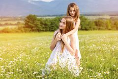 Δύο όμορφες αδελφές στο λιβάδι των chamomiles Στοκ Εικόνες