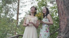 Δύο όμορφες γυναίκες με τα άγρια λουλούδια που στέκονται στα ξύλινα σκαλοπάτια, ομιλία, χαμόγελο Κορίτσια που εξετάζουν την καταπ απόθεμα βίντεο