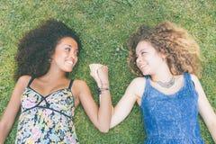 Δύο όμορφες γυναίκες που βρίσκονται στη χλόη Στοκ Φωτογραφίες