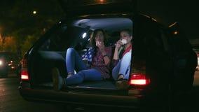 Δύο όμορφες γυναίκες που κάθονται στον ανοικτό κορμό του αυτοκινήτου, που μιλούν και που τρώνε τα burgers κατά τη διάρκεια της νύ απόθεμα βίντεο