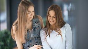 Δύο όμορφες γυναίκες που ψωνίζουν και που εξετάζουν τα storefronts φιλμ μικρού μήκους