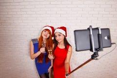 Δύο όμορφες γυναίκες στα καλύμματα Santa που έχουν τη διασκέδαση, πίνοντας τη σαμπάνια Στοκ εικόνα με δικαίωμα ελεύθερης χρήσης