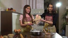 Δύο όμορφες γυναίκες στις ποδιές προετοιμάζουν, κοσκινίζουν το αλεύρι στην κουζίνα απόθεμα βίντεο