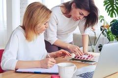 Δύο όμορφες επιχειρηματίες που κοιτάζουν μέσω του καταλόγου του χρώματος palett Στοκ Εικόνες