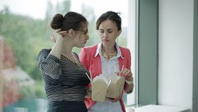 Δύο όμορφες επιχειρησιακές γυναίκες που μιλούν και που τρώνε τα κινεζικά τρόφιμα μεσημεριανού γεύματος που στέκονται στο παράθυρο φιλμ μικρού μήκους