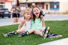 Δύο όμορφες μικρές αδελφές σε έναν κύλινδρο κάνουν πατινάζ Στοκ φωτογραφία με δικαίωμα ελεύθερης χρήσης