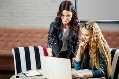 Δύο όμορφες νέες γυναίκες που εργάζονται σε ένα lap-top και που συζητούν τα επιχειρησιακά ζητήματα Στοκ Εικόνα